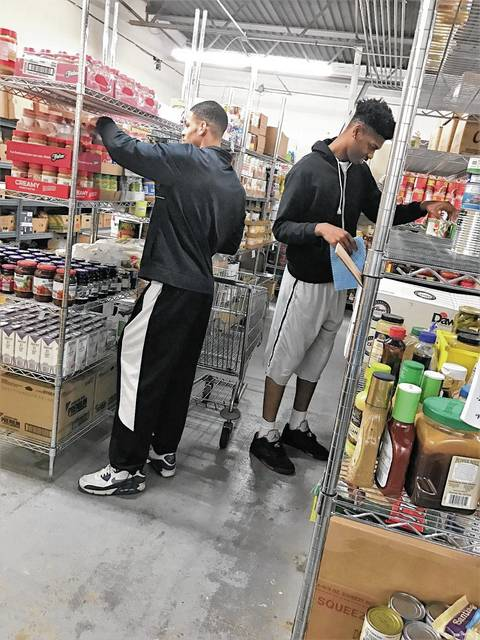 Malik Jacobs, left, and Justin Johnson, right, are two of the 16 UU students who volunteered at the Caring Kitchen.