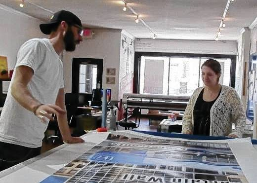 Streamline Graphic and Print owner Mike Short explains a promotional piece and the process of creating it to Graham High School junior Laura Campbell.
