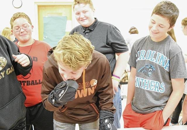 Triad seventh graders glimpse what it's like to deal with disabilities May 19, with tasks made tougher than they would be otherwise. Here, Skyler Griffith, middle front, tries to open a piece of candy with gloves, to simulate mobility difficulties. Also pictured, from left, are Aaron Silverstein, Trey Beckley and Evan Culp.