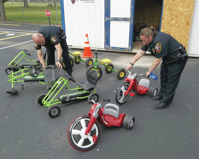 Urbana Police Officers Mike Cooper and Kerrie Kimpel inspect items ahead of the Urbana Police Division's annual Safety Town program. This year's classes will be held on June 5 through 9 and June 12 through 16