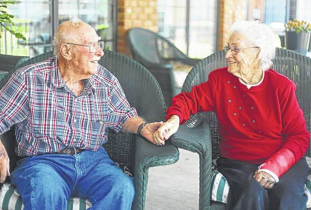 Melanie Boyd/Times-Georgian   Joseph Buroker holds his wife Jean Buroker's hand on the porch at The Oaks in Carrollton. The couple will celebrate their 77th wedding anniversary on May 19.