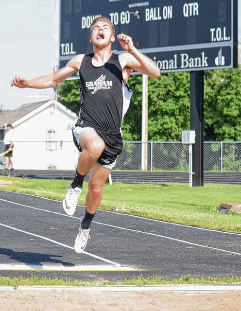 Graham's Tyler Powell launches himself into the air during the long jump competition at the Division II district track and field preliminaries on Thursday.