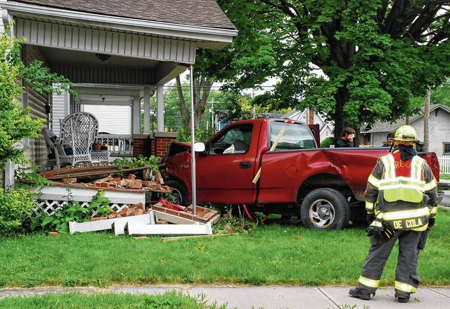Urbana firefighter/paramedic Jonathan De Cola looks at the aftermath of a two-vehicle crash just after 4 p.m. on Wednesday. A Ford F-150 pickup truck crashed into the front porch at 231 East Lawn Ave. in Urbana. The crash took place at the intersection of East Lawn Avenue and East Church Street.