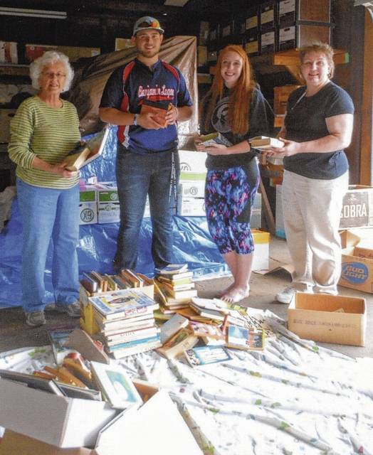 After a long afternoon of sorting books, four persons remained to complete preparing the C.A.R. boxes for loading. From left are Judith Henson, Conner Caudill (friend of the group), Camille Brinnon and Kim Snyder.