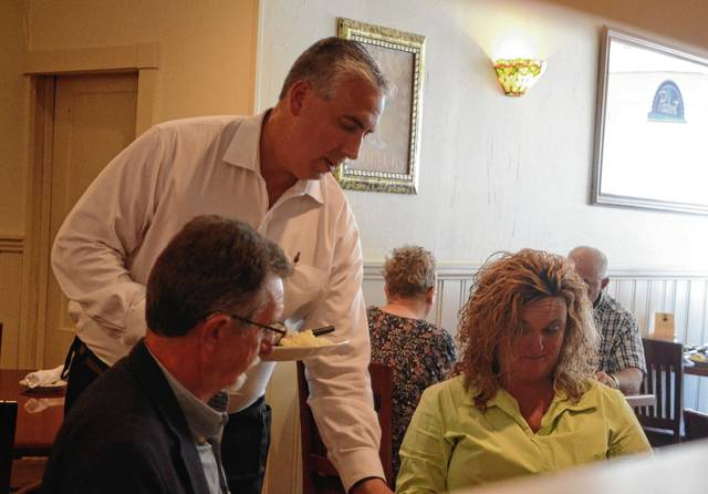 Champaign County prosecutor Kevin Talebi serves food during the annual Celebrity Waits for Tips to benefit the American Cancer Society on Tuesday at Coppertop.