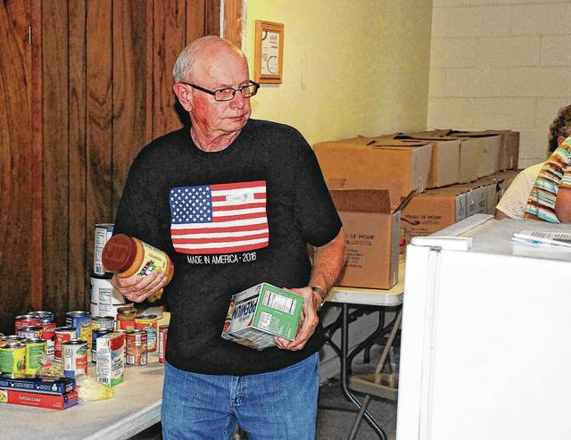 Mechanicsburg resident Loren Scheiderer helps fill a box of food during a recent distribution day at the Oasis of Mercy Food Pantry, which operates out of St. Michael's Parish Hall at 40 Walnut St. in Mechanicsburg.