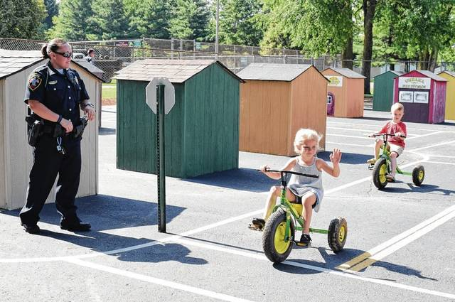Urbana Police Officer Kerrie Kimpel oversees bike safety lessons during Safety Town at Melvin Miller Park on Friday. Students Makayla Wagner and Lyle Rice learned the rules of the road, school bus safety and avoiding strangers, among other lessons.