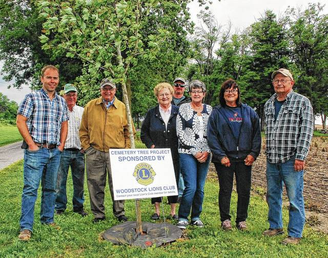 Several members of the Woodstock Lions Club pose in front of a maple tree the club recently had planted in Woodstock Cemetery as part of its Cemetery Tree Project. Pictured, left to right, are Andy Heath, Ed Phillips, Bill Donohoe, Jackie Hayes, Dave Corbett, Kathy Williams, Susie Finley and Daryol House.