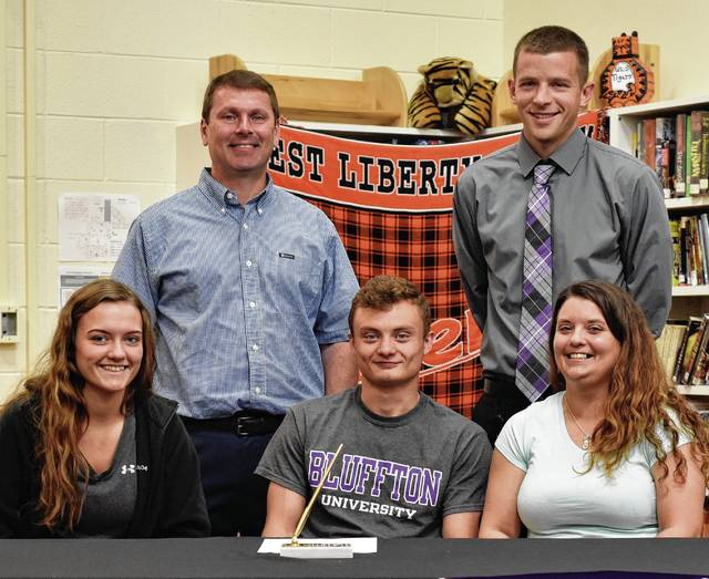 Christian Parker signed his letter of intent to play soccer at Bluffton University in the fall. He is pictured with his mother and sister, along with his coaches, Tim Wolfe and Joe Taylor.
