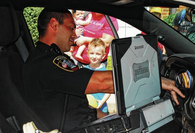 Urbana resident Owen Meadows, 4, gets an up-close look inside an Urbana Police Division (UPD) cruiser as Officer Brandon McCain shows him how to turn on the lights and siren during a Touch-A-Truck event held Thursday at the Champaign County Library. Along with the UPD, participants in the event included the Urbana Fire Division, Champaign County Engineer's Office and Koenig Equipment.