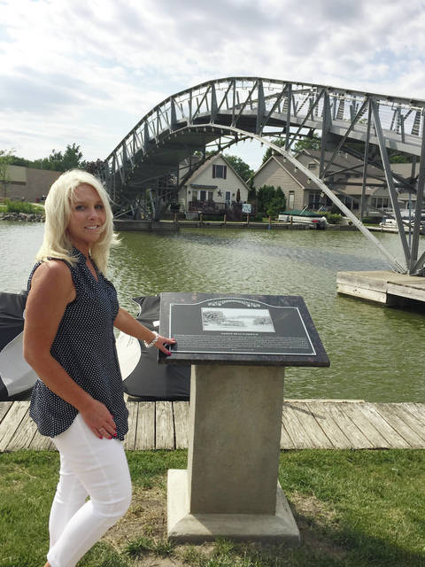 Indian Lake Area Historical Society Trustee and Sandy Beach Bridge Committee Chairperson Julie Schrader proudly displays one of the 11 new historical markers placed at the Russells Point Harbor bridge pathway.