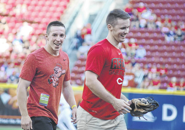 Corey Bogan, left, and his brother Matt walk off the field at Great American Ball Park Friday night laughing about Corey's ceremonial first pitch, which was just a little off the mark.
