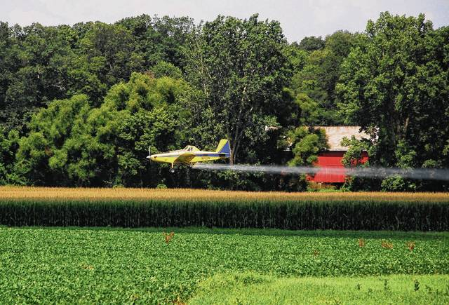 An agricultural airplane spent Tuesday morning spraying fields just outside Urbana between South U.S. Route 68 and state Route 54. Pictured is the plane in action over a field on the west side of state Route 54 between Campground Road and East Powell Avenue.