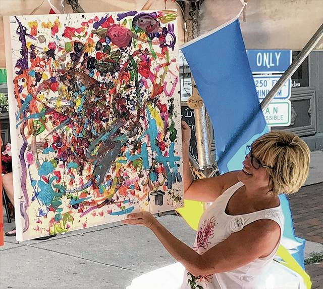 Every year, the young artists in the Kids' Tent get together and create a community painting. Shelly Herrmann prepares to hang the 2017 Jackson Pollock-inspired piece that visitors created on the spot Saturday in Monument Square.