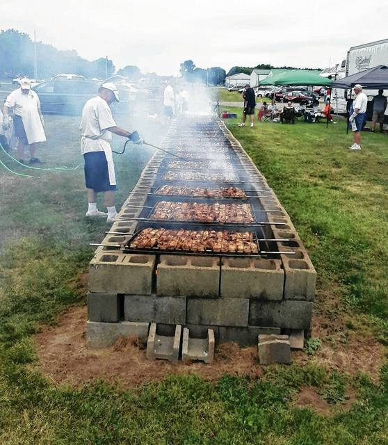 As this photo from last year shows, it can get a bit smoky for the Rotarian chefs cooking up the Fourth of July feast.