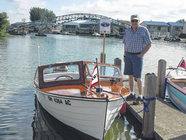 Roland Clark of Greenville stands with his 1958 Lyman 15-foot wooden boat with a 40 hp motor.