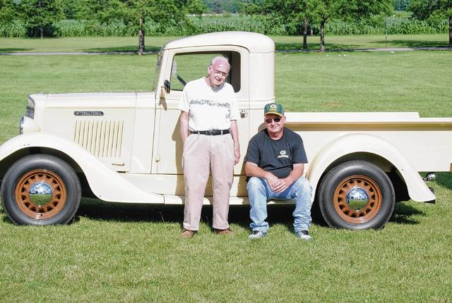 Max Boyer of rural Cable (left) and his son, Lloyd, pose next to the 1935 International they restored together after the truck sat unused in a garage for 40 years. The Boyers were on hand for the Car & Motorcycle Show at Lions Park in West Liberty as a part of the village's Bicentennial celebration over the weekend.