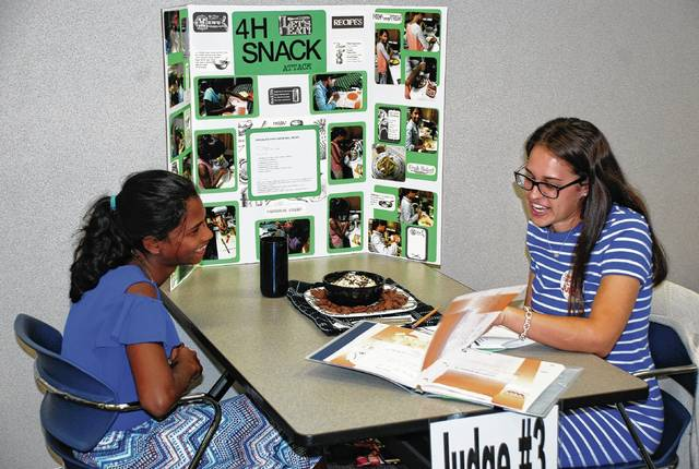 Tori Elleman (left) discusses her Snack Attack project with judge McKenzie Pruitt during Champaign County Fair pre-judging at the Champaign County Community Center earlier this month. The Champaign County Fair is Aug. 4-11. Awards for pre-fair judging will be presented during the fair.