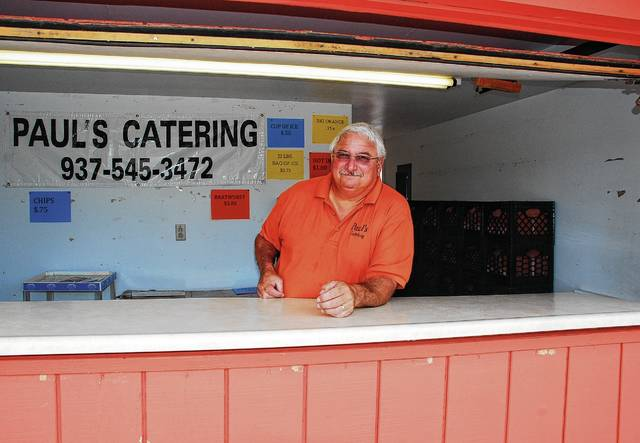 Urbana resident and business owner Paul Poppel stands behind the counter of his fair concession booth in the Big Orange Building across from the Merchants Building at the Champaign County Fairgrounds. The booth, which will open on Friday, Aug. 4, under the new name of Paul's Catering, will continue offering fairgoers one of the traditional drinks of the county fair – Big Orange.