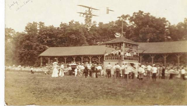 This postcard photo was taken from the infield toward the grandstand at the Champaign County Fair on July 4, 1911. An airplane (most likely a Wright flyer) flies over the grandstand on the occasion of a Chautauqua being held on the fairgrounds. A Chautauqua is a type of educational extension by means of lectures, summer schools and concerts modeled after one such school established in Chautauqua, New York, in 1874. Until about 1904, local Chautauquas were held in the Chautauqua Hall (#A171-2) at the campground on Campground Road, south of Urbana. This grandstand was replaced by the current grandstand in 1949. (Champaign County Historical Society #A1704)