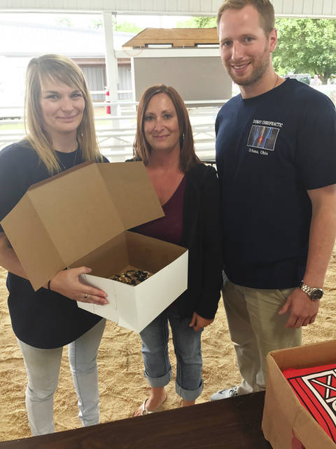 Lori Purk, middle, poses with her Cookies n' Cream pie alongside Brittany Wardwick and Dr. Scott Kayatin of the Donay Chiropractic Life and Wellness Center, which purchased Purk's pie for $600. The pie earned Purk the Overall Grand Champion award in this year's contest.