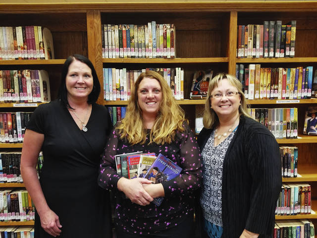 Champaign County Republican Party Chairwoman and member of the Champaign County Republican Women's Club (CCRWC) Audra Bean (left) and the Women's Club President Kathy DeWeese (right) present Saint Paris Public Library Director Nichole Rush (center) with a donation of books from the CCRWC.
