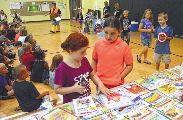 Second graders Sarah Barnes, left, and Ava Phillips, right, choose a new book during the Summer Reading Celebration at Indian Lake Elementary School.
