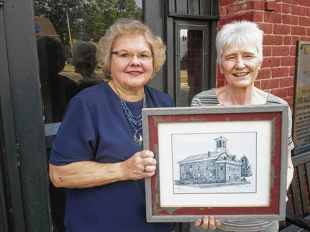 Historical Society President Donna Lou Erwin (left) presents Marianne Birt with a framed town hall print by Urbana artist Mike Major.