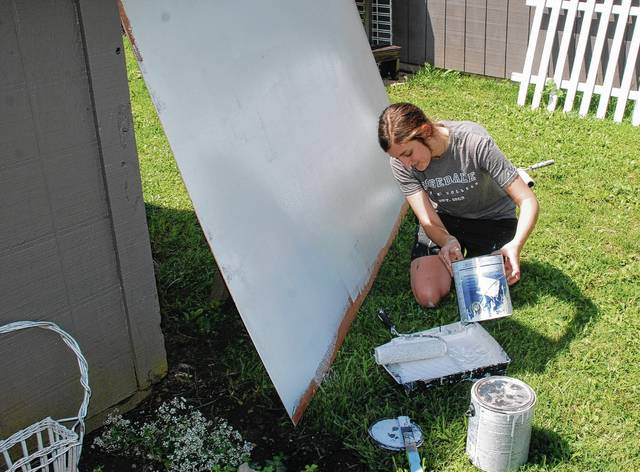 Emilie Miller paints a blank background for attendees of the Madden Road Music Fest to adorn on Saturday. The progressively painted mural is part of the activities of the festival and those who attend are invited to contribute by painting their own design on the larger mural that begins with a gray background. The annual festival was held Saturday afternoon and evening on Madden Road.
