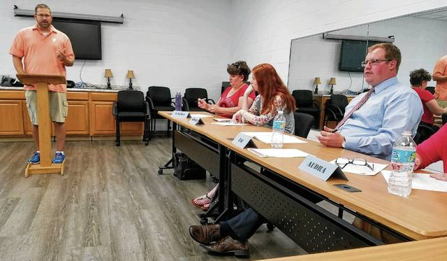 Greg Hower speaks at the podium during a Toastmasters meeting at the Champaign Family YMCA. Also shown are, from left, Laura Alban, Kristi Purtee and Zac Fiely.