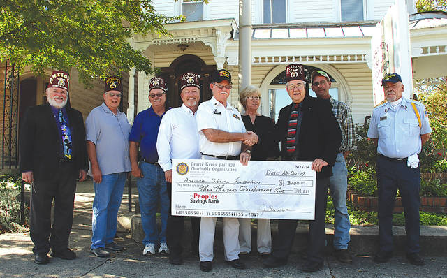 Post Commander Jesse Brewer shakes hands with Steve Brown, president of the Antioch Shrine Foundation, on Oct. 20 in front of American Legion Pearce Kerns Post 120 as he presents a $3,100 check for the foundation. Also pictured are, from left to right, Bret Stahler, Chief Rabban of the Antioch Shrine, Shriners Dennis Todd, Bill Instine and Rob Butler, Ladies Auxiliary representative Joyce Coy, Sons of the American Legion representative Jeff Wilkins and member Ron Cook.
