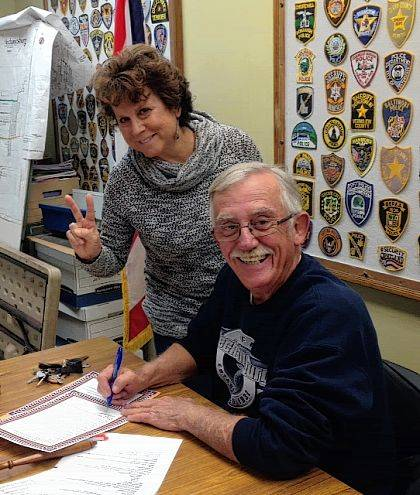 Greg Kimball signs a Mechanicsburg proclamation at the Village Council meeting on Oct. 16 with Debra Walters by his side.