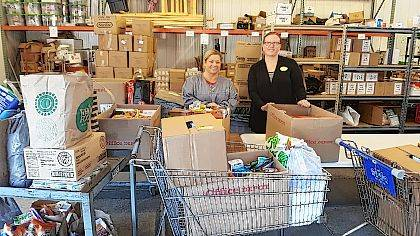 """Amy Jo Black, left, and Melanie Bisdorf presented The WhereHouse food ministry of the Urbana United Methodist Church a gift of 1,000 pounds of food and personal care items collected by Kindred at Home and Kindred Hospice of Dayton. """"This generous donation goes a long way in furthering our efforts to serve local families who need assistance and encouragement,"""" Ted Herndon, director of The WhereHouse, said."""