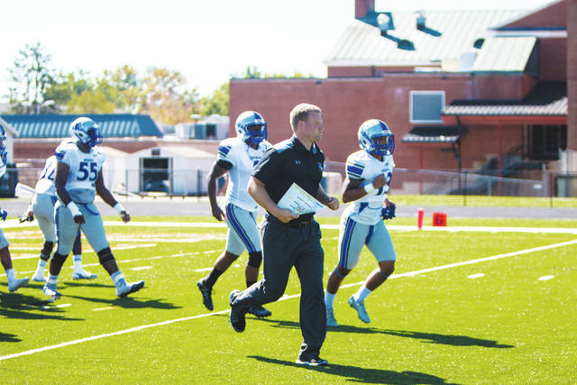 UU Coach Tyler Haines (pictured) leads the Blue Knights onto the field prior to a recent game.