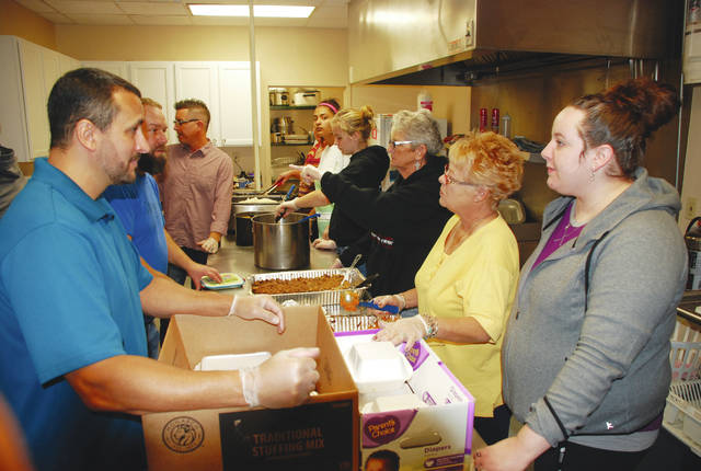Volunteers line both sides of a preparation table at the Caring Kitchen on Thanksgiving in Urbana. The volunteers were filling containers for carryout diners. More than 500 meals were prepared for serving and a sit-down dinner was available at the Caring Kitchen from 11 a.m. to 12:30 p.m. Food deliveries were made between 10:30 a.m. and 12:30 p.m. This was the 27th year the Caring Kitchen provided a Thanksgiving meal, which consisted of turkey, dressing, green beans, mashed potatoes, sweet potatoes, dinner rolls, cranberry sauce and pie. On the west end of the county, the St. Paris Federation of Churches served Thanksgiving Day dinner from noon to 1:30 p.m. in the cafeteria at Graham Elementary School.