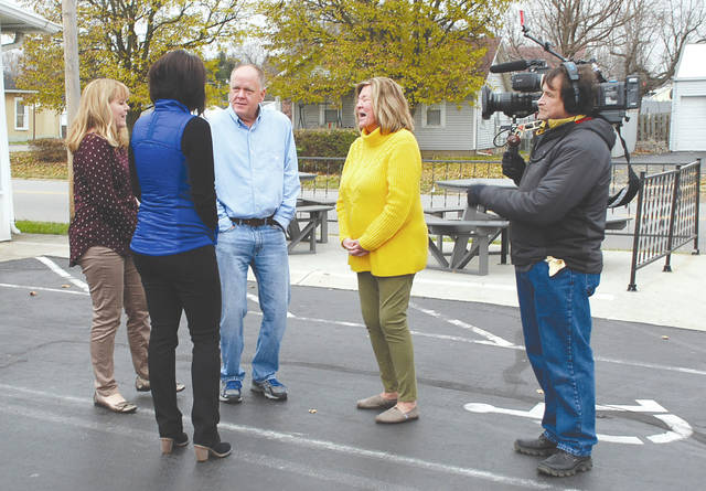 """A cameraman for CBS Sunday Morning records Urbana native Traci Bild (back to camera) as she meets with (left to right) Deborah Doupnik, Scott Woodruff and Tami Shade, the three children of former Dairy Queen owners Jug and Jerri Woodruff, on Thursday at the Dairy Queen on North Main Street in Urbana. Bild titled a blog for the Huffington Post """"A Few Coins, a Random Act of Kindness and a Christmas Tree,"""" in which she told how Jug gave her a Christmas tree when she was 7 years old. Bild said her story is to be featured on an episode of CBS Sunday Morning with Jane Pauley this month."""