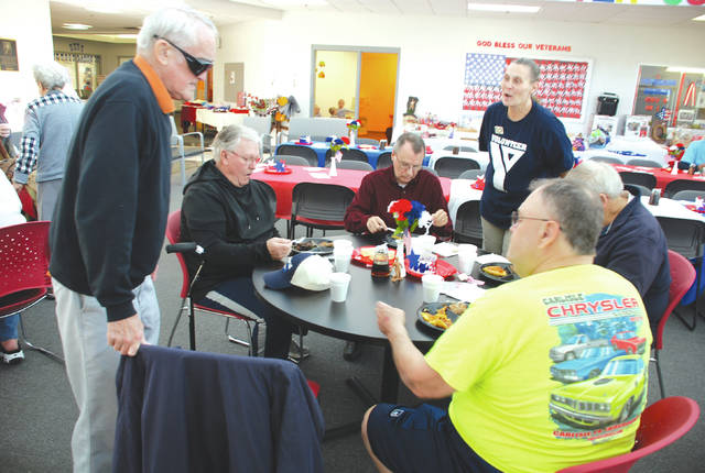 Army veteran Carl Tilkington takes his seat at a table with fellow veterans Freddie Webb, Bob Welch, Fred Marshall and Larry Oglesbee while Champaign Family YMCA volunteer Lori Figley offers to serve them at the YMCA's Veterans Memorial Brunch on Thursday.