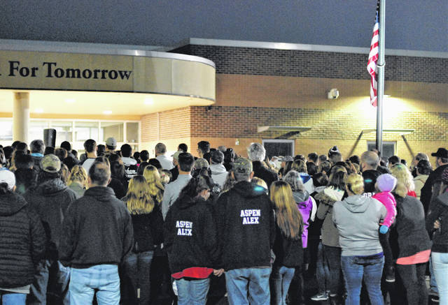 Community members gather for a candlelight vigil in memory of Sara M. Hess in front of Graham High School on Saturday evening.