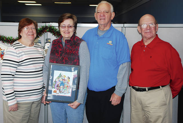 "Pictured from left are Eileen James, Joann Evans, Al Evans and Neil Evans. James and Neil Evans are volunteers with the Cancer Association of Champaign County (CACC). Joann and Al Evans are holding the custom-drawn 'Dennis the Menace"" cartoon panel created by artist Ron Ferdinand especially for them after Al won a raffle benefitting the CACC."