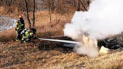 Firefighters extinguish a blaze that started when a vehicle flipped over a South U.S. Route 68 guardrail on Thursday.
