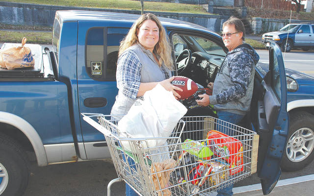 Tara Jordan, assistant director of the Caring Kitchen, accepts a donation of about 40 toys, as well as canned goods, from the commander of American Legion Post 120, Jay Brewer, on Dec. 20.