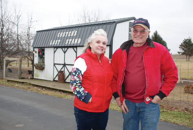 Midge and Robert Custer stand near one of the out-buildings on their mini-farm on Parkview Road. The tongue-in-cheek message on the roof behind them could foreshadow Downsize Farm's entry into the latest chapter of the Buckeye Wind saga. Downsize Farm is a Medicaid-certified facility for developmentally-disabled persons. The Custers are concerned about how the operations of a wind farm with turbines sited to the east and the west of them might adversely affect their clients.