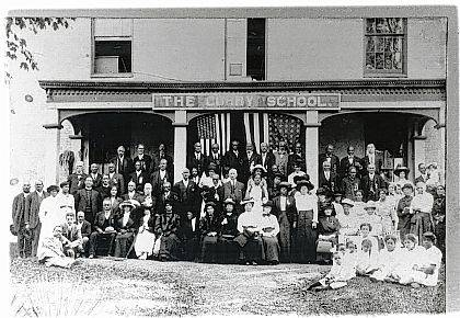 "This ""Then"" photo of The Curry School was taken on the occasion (Sept. 20, 1913) of the reunion of black Civil War veterans and widows, sons and daughters from all parts of Ohio (Urbana Daily Citizen). Professor Elmer Curry is on the grass at the extreme left. This building at 325 E. Water St. was originally a residence owned by Philander B. Ross. It was purchased by the Urbana City Board of Education, which used it until 1898. Then Professor Curry acquired the property and moved the Curry Normal and Industrial Institute into the building. Over 2,000 mostly African-American students, youth and adults, were instructed in industrial skills, higher academics, and morality at the Institute. (Source: Sherry Virts, Champaign County Preservation Alliance)"
