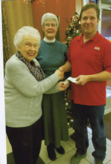 Doug Williams, right, presents a check for start-up capital costs to CCCRP LLC President Janet Ebert and Treasurer Janet Evans, center.