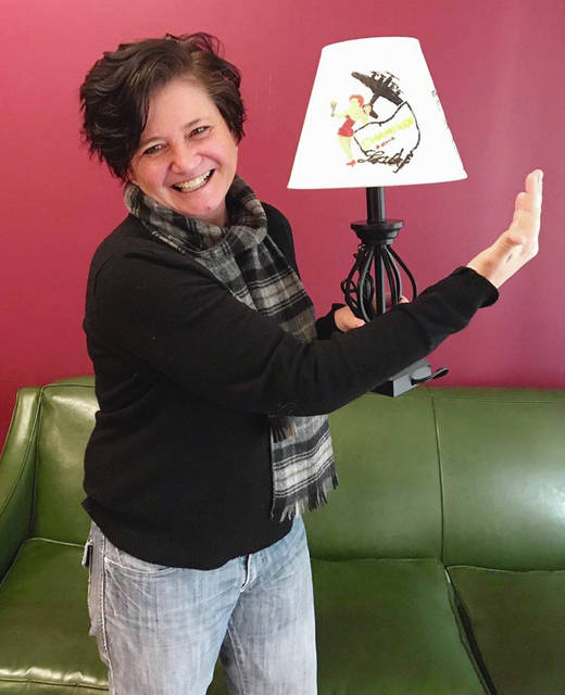 "Beth Adair shows off her ""Bad Art by Good People"" entry for 2018. The lamp is a salute to local aviation history and depicts the Champaign Lady B-17 Flying Fortress under restoration at Grimes Field."