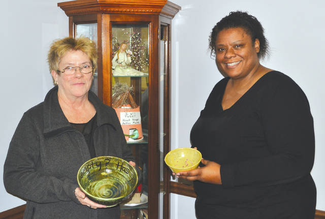 """Second Harvest Development Director Rosemary Bradley, left, and Executive Director Tyra Jackson hold two of the """"empty bowls"""" that will be filled with soup at this year's Empty Bowls event on March 1."""