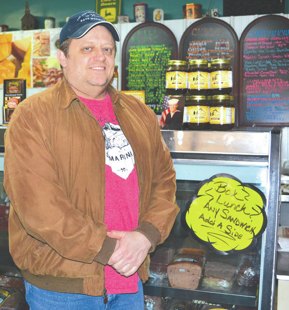 Jason Mefford stands beside a display of his marinades at Char's Market and Kitchen in St. Paris.