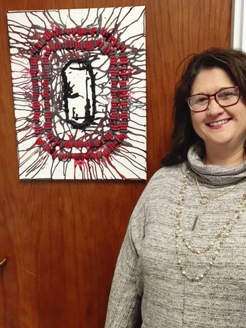 Melinda Morrison stands with her Buckeye-inspired art. Morrison works at The Ohio State University Extension Office in Champaign County.