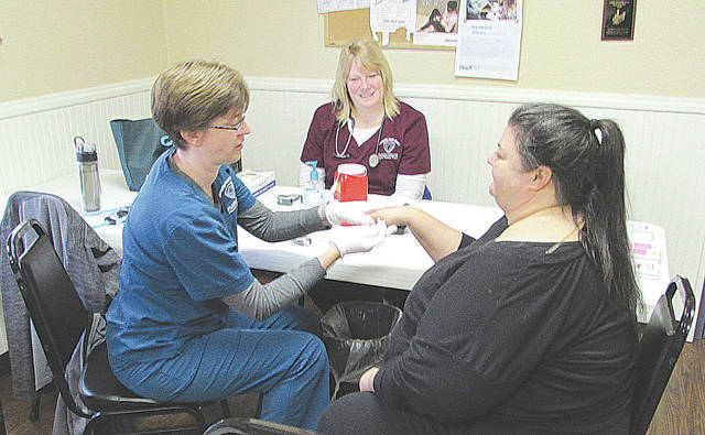 From left to right: Nurses Karrie Cordial and Hope Stickley from Champaign County Health District perform a blood sugar count on Caring Kitchen resident Lori Dodds on the day of the point-in-time count, Jan. 23.
