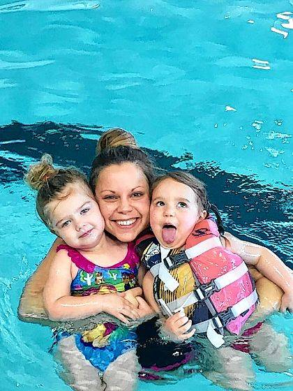 Members Leilah Smith and Jennifer and Eva Post enjoy the swimming pool at the Champaign Family YMCA.